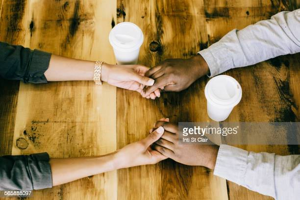 Black couple holding hands at wooden table,