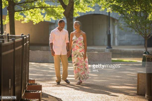 Black couple holding hands walking in park