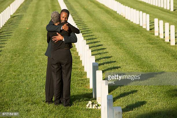 Black couple hugging at military cemetery