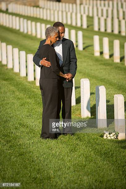 Black couple hugging in military cemetery