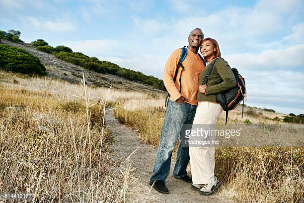 Black couple hugging on rural path