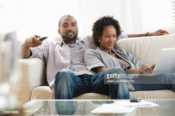 black couple on sofa using laptop and watching television - changing channels stock photos and pictures
