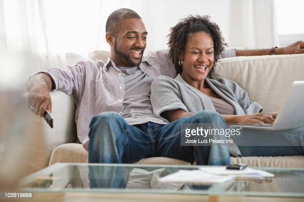 Black couple on sofa using laptop and watching television