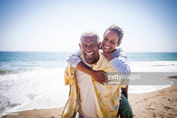 black couple piggyback on beach - active senior woman stock photos and pictures