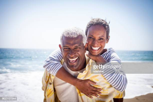 black couple piggyback on beach - hot love stock pictures, royalty-free photos & images