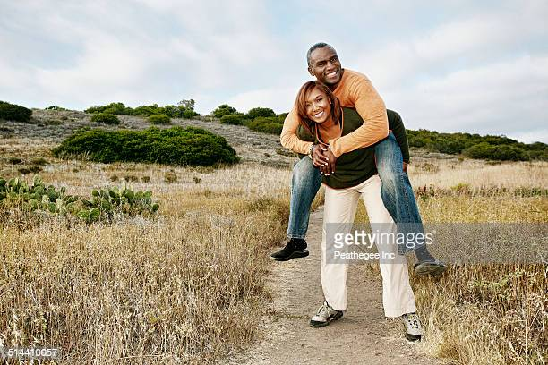 black couple playing on rural path - piggyback stock pictures, royalty-free photos & images