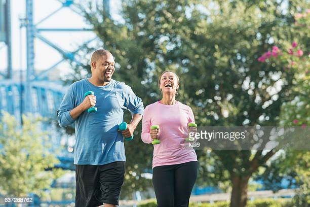 Black couple running together in park, laughing