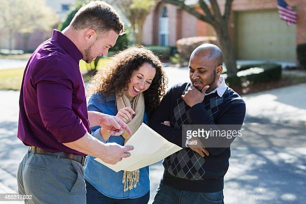 Black couple standing on residential street with agent