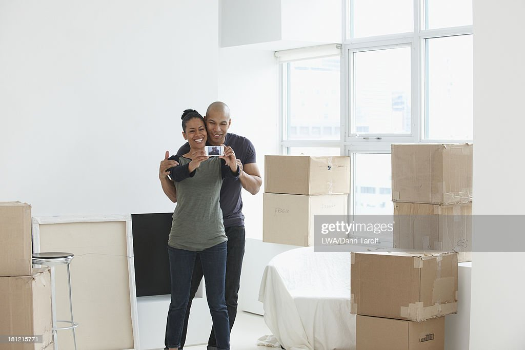Black couple using cell phone in new house : Stock Photo