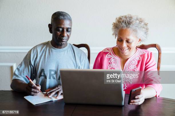 Black couple using laptop and cell phone at table