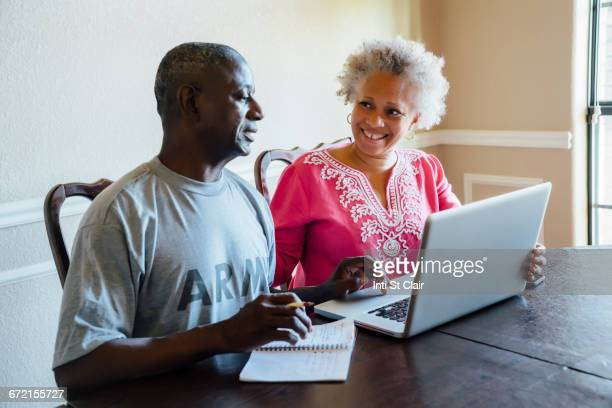 Black couple using laptop at table