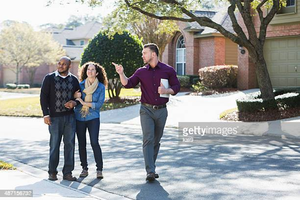 Black couple walking on residential street with agent