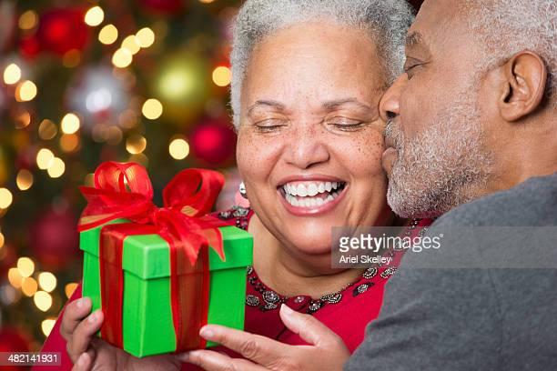 black couple with christmas gift kissing - de amado carrillo fuentes fotografías e imágenes de stock