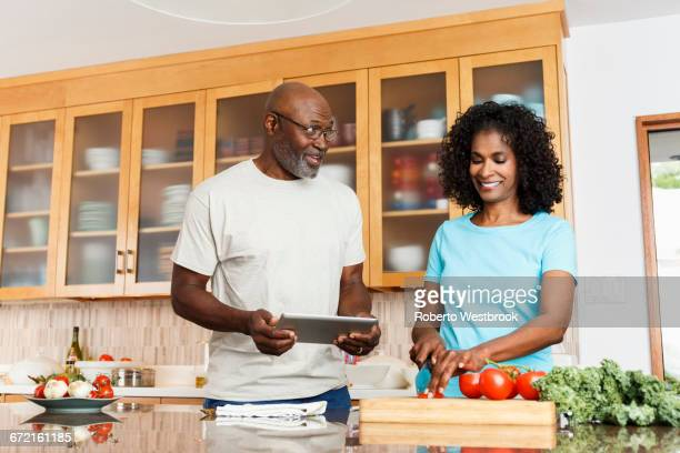 Black couple with digital tablet chopping tomatoes in kitchen