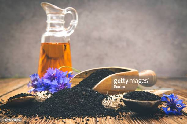 black cumin seeds essential oil with wooden spoon and shovel on wooden background - black seed oil stock pictures, royalty-free photos & images