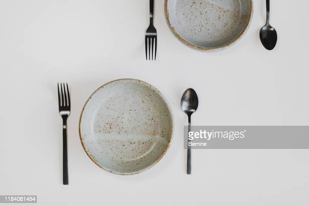 black cutlery and pottery plate on a white background - eating disorder stock pictures, royalty-free photos & images