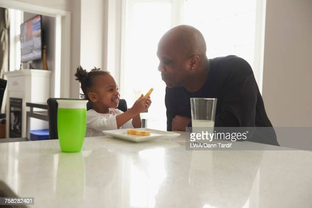 Black daughter offering food to father
