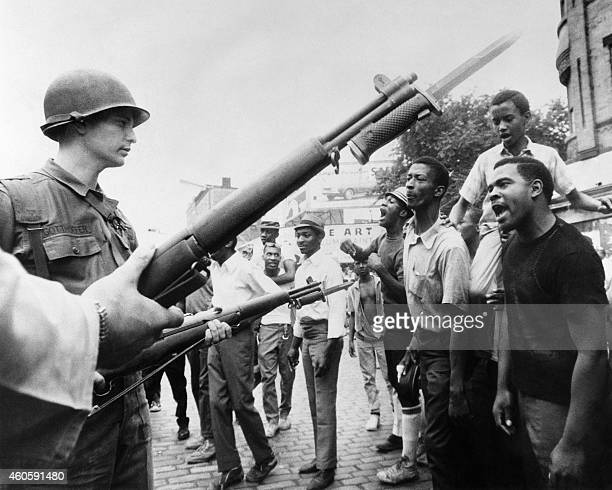 Black demonstrators face armed federal soldiers in Newark on July 17 1967 during riots that erupted in the town following a police operation / AFP /...