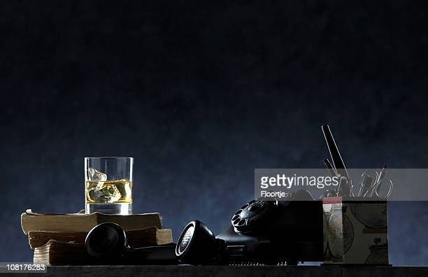 black: desk with pens, pencils, books and glass of scotch - film noir style stock pictures, royalty-free photos & images