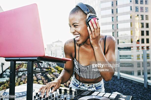Black DJ laughing on urban rooftop