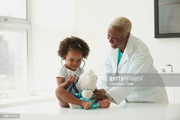 black doctor examining girl - pediatra - fotografias e filmes do acervo