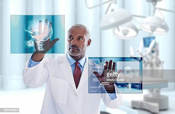 Black doctor looking at digital display in doctor's office