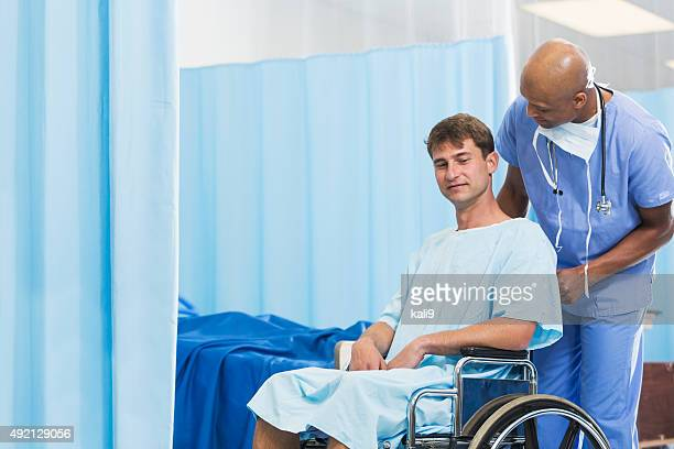 Black doctor or nurse with patient in wheelchair