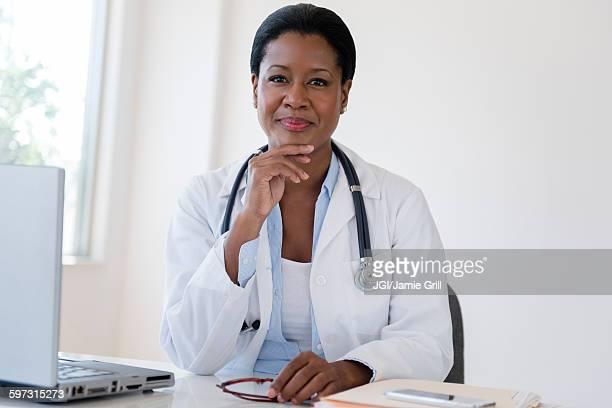 Black doctor sitting at desk
