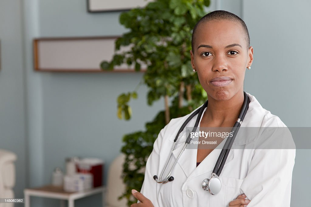 Black doctor standing in doctor's office : Stock Photo