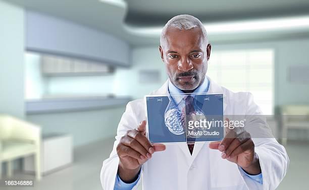 Black doctor using digital display in doctor's office