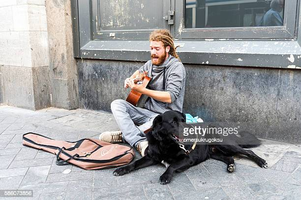 Black dog and street musician is playing guitar in Amsterdam