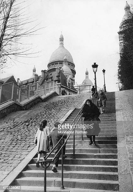 'A black dressed woman descending the staircase dominated by the SacrCoeur Basilica in Montmartre on the left backwards two children are coming up...