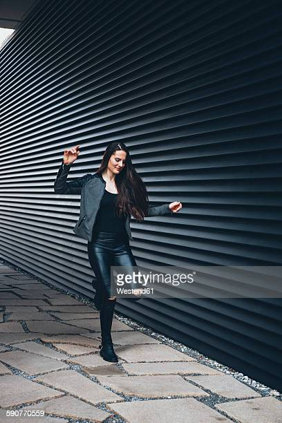 Black dressed young woman hopping on one leg in front of black facade