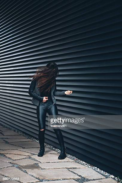 Black dressed young woman standing in front of black facade playing air guitar