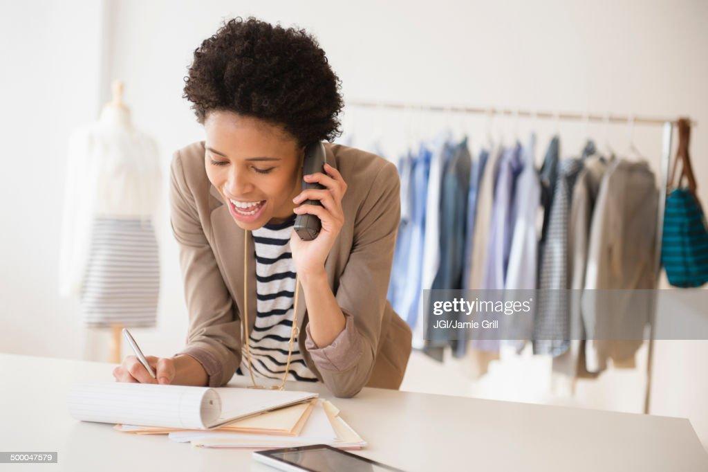 Black dressmaker talking on phone in studio : Stock Photo