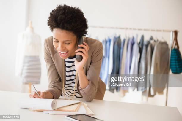 Black dressmaker talking on phone in studio