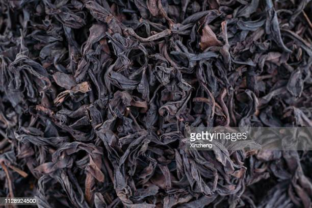 black dry tea leaves close up for background - tea leaves stock photos and pictures