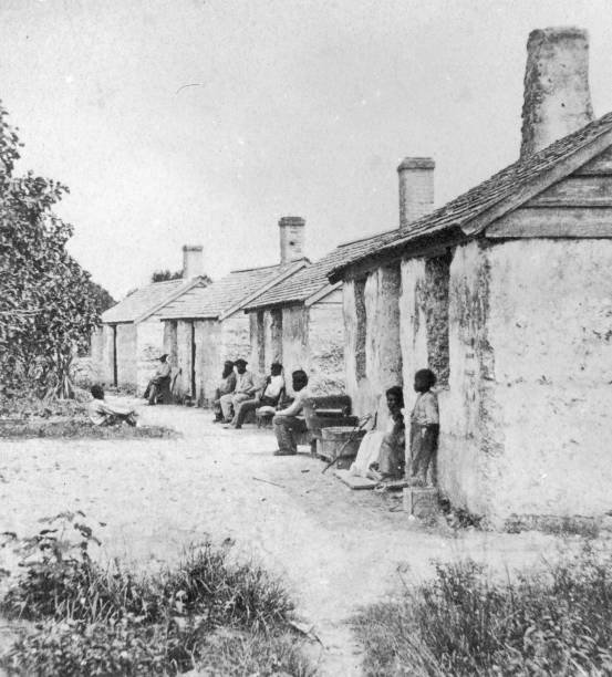 Black Slaves sit outside of their Quarters in Ft, George...
