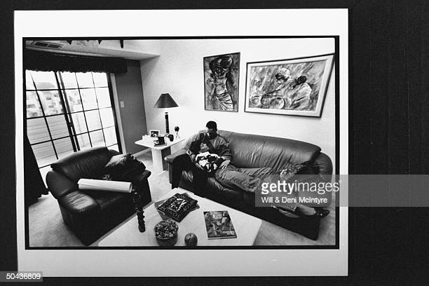 Black Entertainment TV's floating anchorman Ed Gordon snuggling w his pregnant wife Karen while relaxing on leather couch in living rm at home