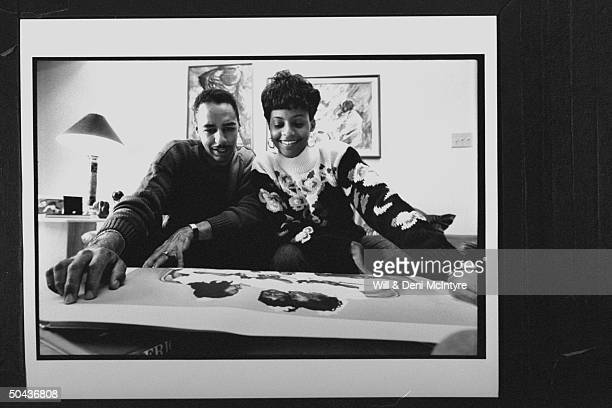 Black Entertainment TV's floating anchorman Ed Gordon w his pregnant wife Karen looking over a ptg they just purchased as they relax on couch at home