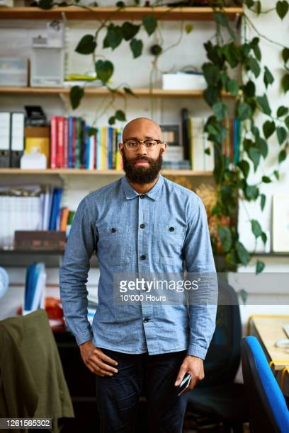 black entrepreneur in office looking at camera - positive emotion stock pictures, royalty-free photos & images