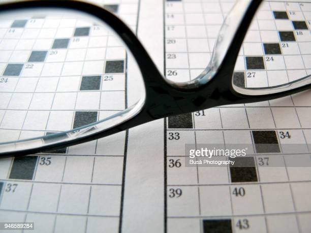 black eyeglasses on crossword puzzle - myopia stock photos and pictures