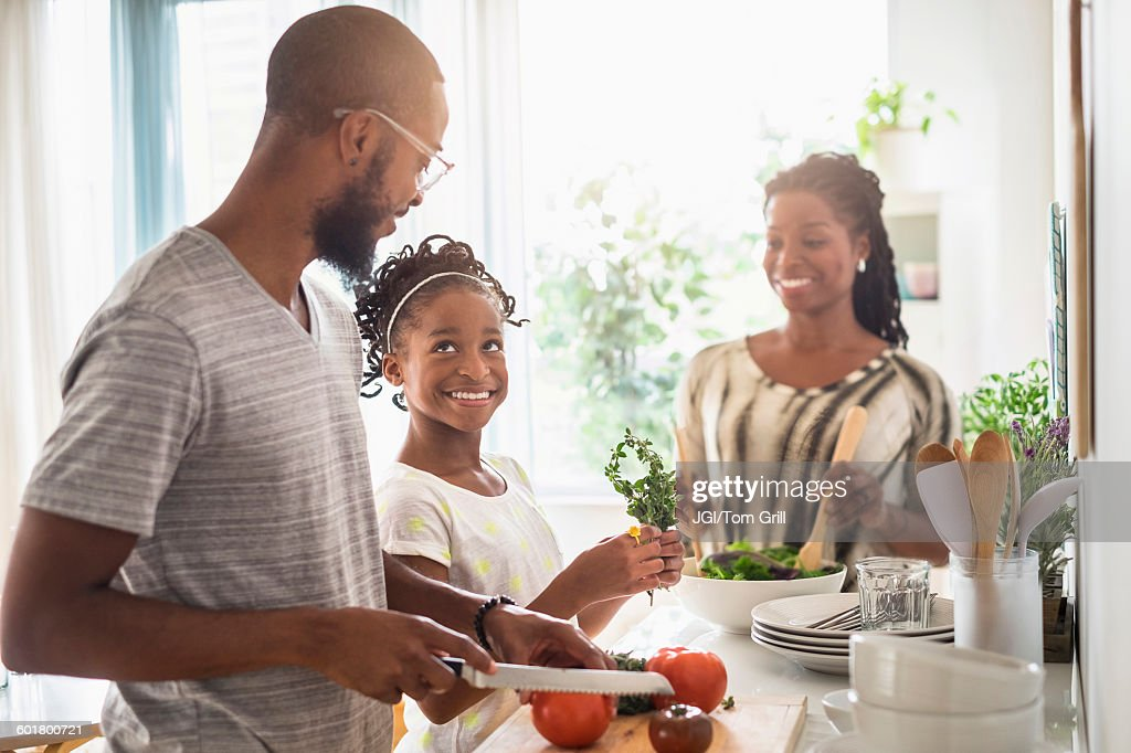 Black family cooking in kitchen : Stock Photo