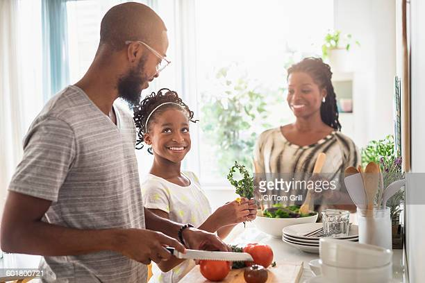 black family cooking in kitchen - black family dinner stock photos and pictures