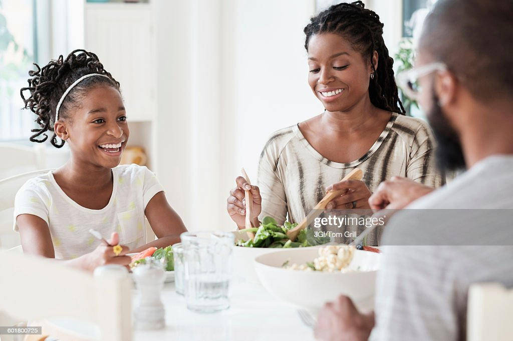 Black Family Eating Salad At Table