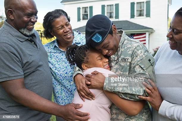 Black family greeting returning female soldier