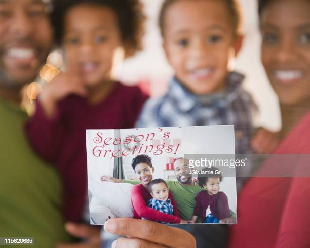 Black family holding Season's Greetings photograph