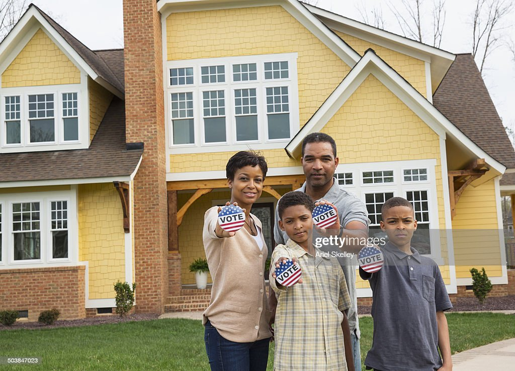 Black family holding Vote buttons outside home : Stock Photo