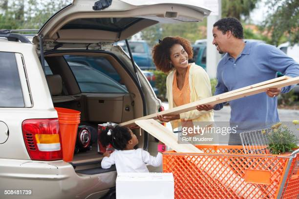 Black family loading car at home improvement store