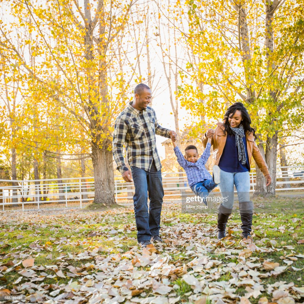 Black family playing in autumn leaves : Foto stock